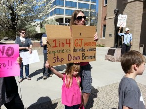 """A woman attends the rally at Grand Junction City Hall to protest Richard Brainard taking office. Brainard has admitted he struck his live-in girlfriend to get her to """"shut her mouth."""""""