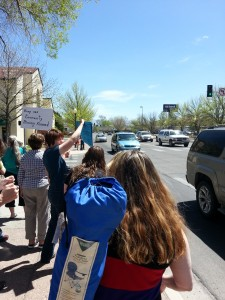 "Grand Junction citizens protest in front of the Chamber of Commerce. The blue sign says ""GJ Chamber endorses violence."""