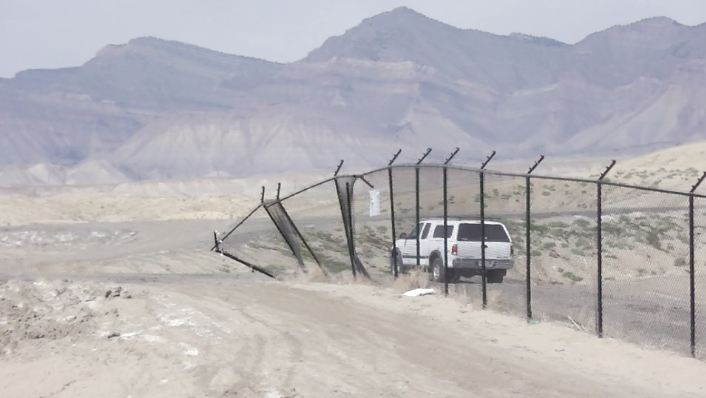 "The Grand Junction Regional Airport's multi-million dollar, electrified, biometric-access-only  ""Security Fence"" ends out in the desert north of the airport. The fence surrounds the airport on three sides. The remaining side is fenced with an old, three-strand barbed-wire fence (Photo credit: Anonymous, taken April 7, 2014)"