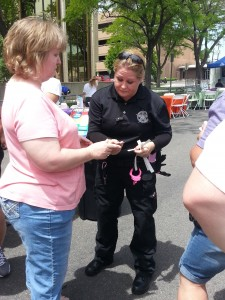 A female security guard sports pink handcuffs as she checks IDs to get into the beer garden at the 2014 Grand Junction Gay Pride Street Fest