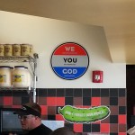 "Jimmy John's ""God"" sign, alongside a giant pickle"