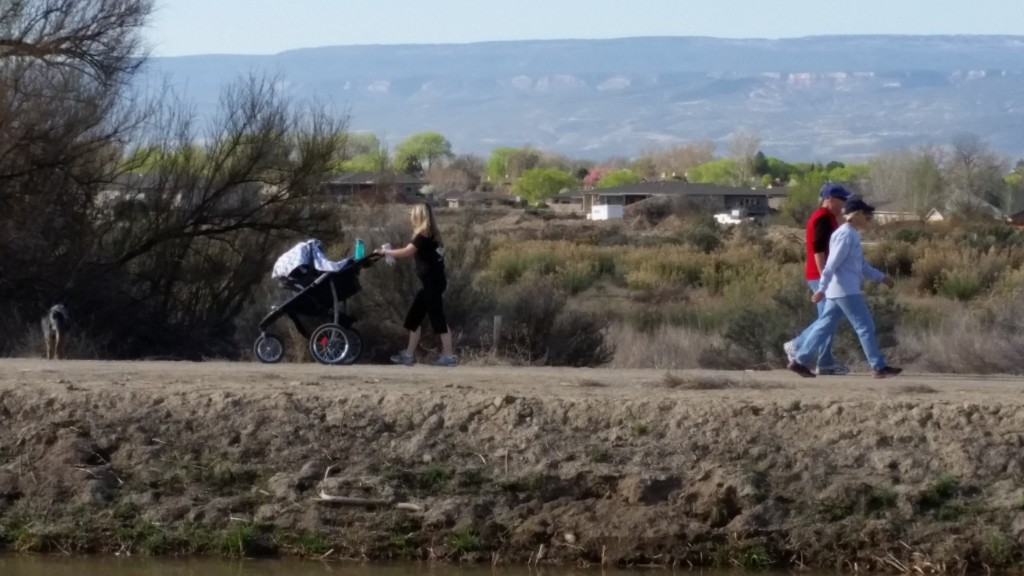 People enjoy a morning stroll by the Government Highline Canal as it fills the valley's massive, government-built irrigation system with water, marking the beginning of the 2015 growing season in the Grand Valley