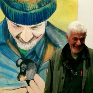 Mel in front of an original painting of him with a puppy, by his wife, art teacher Vera Mulder